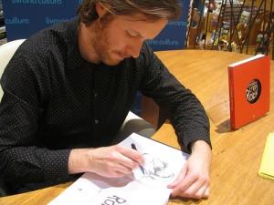 Bouris desenhando o vocalista do U2, Bono, em versão anos 90, em livro